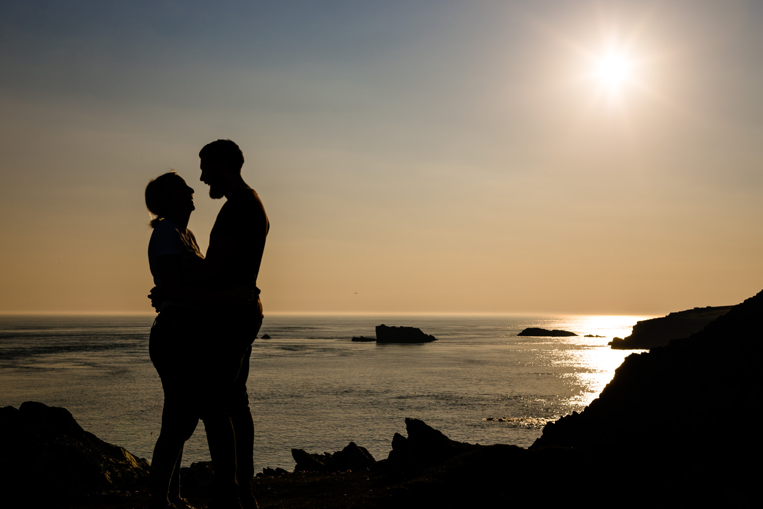 A couple's silhouette against the golden hour sunset on a pre wedding shoot, Anglesey wedding photography