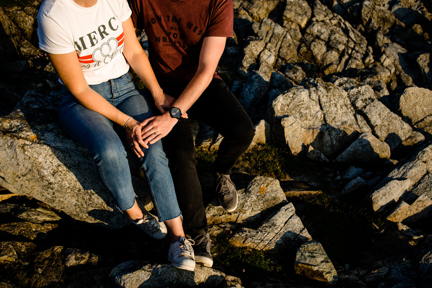Detail of a couple holding hands sat on the Anglesey headland.