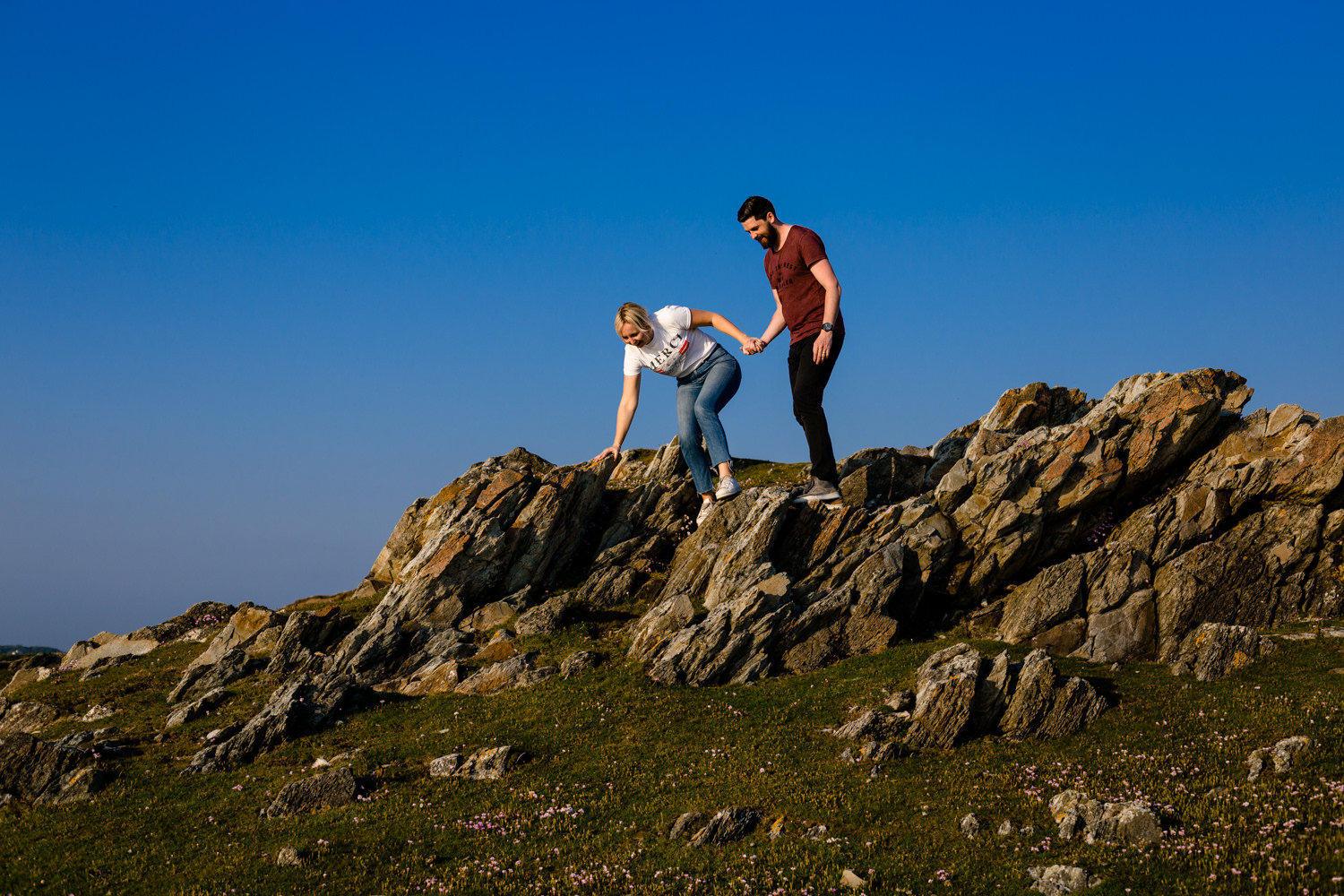 Katie & Sean climb over the rocks on a pre wedding shoot in Anglesey.