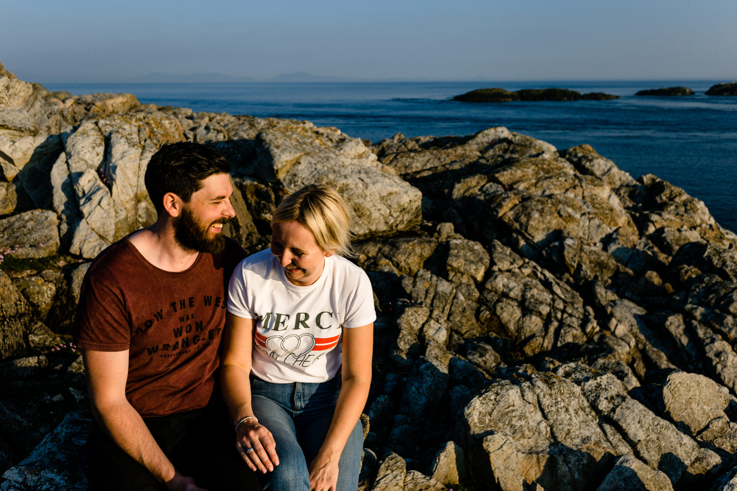 Anglesey Wedding photographers capture a couple laughing together on the headland rocks.