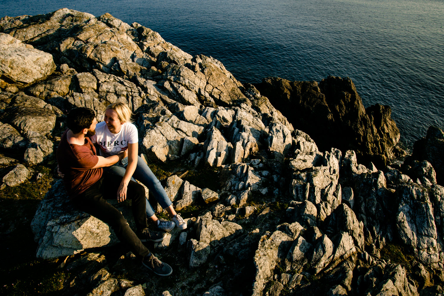 A view down the cliff rocks in Anglesey, of a couple sat cuddling.