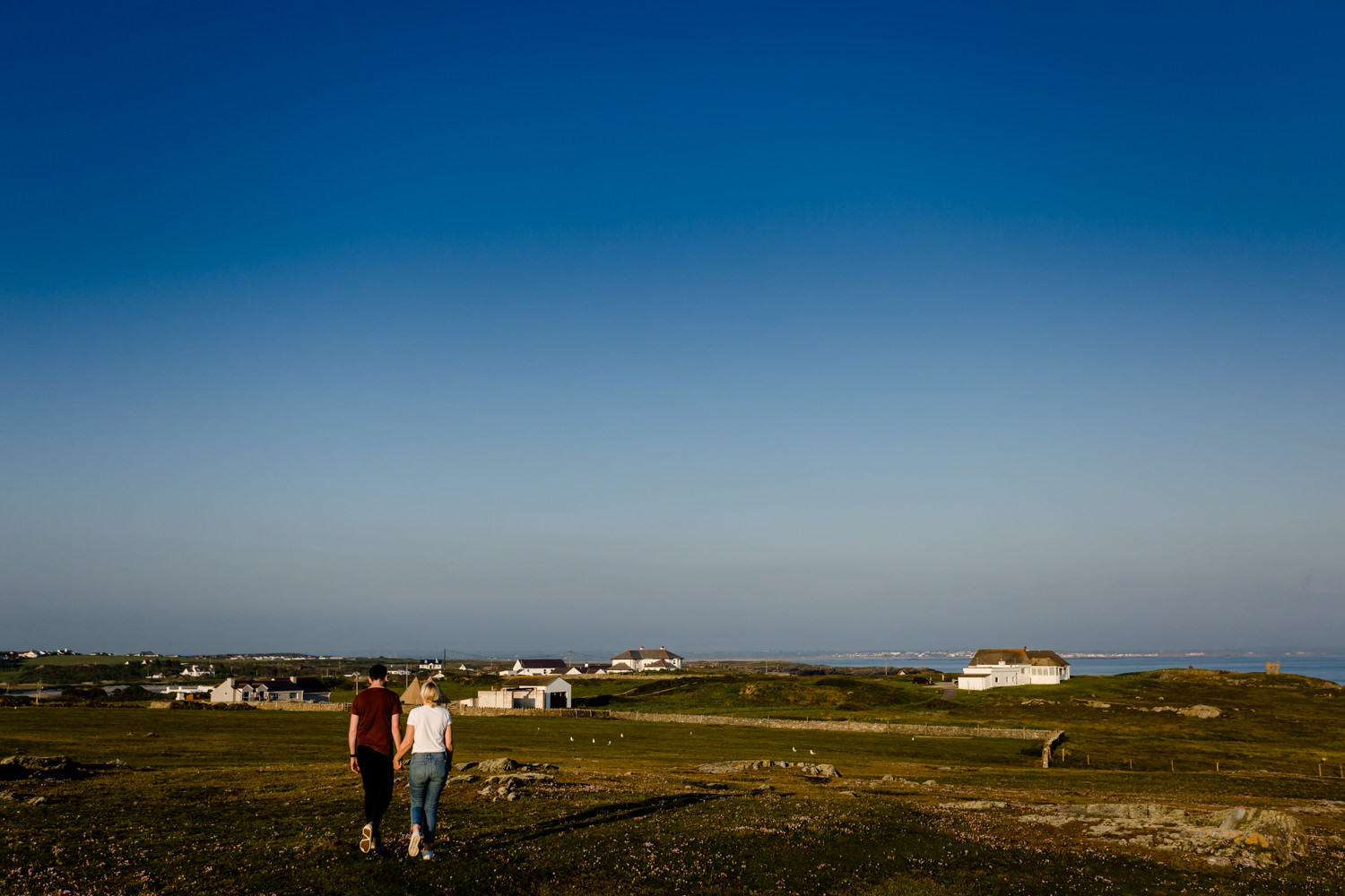 An engaged couple walking along the Anglesey headland by wedding photographers.