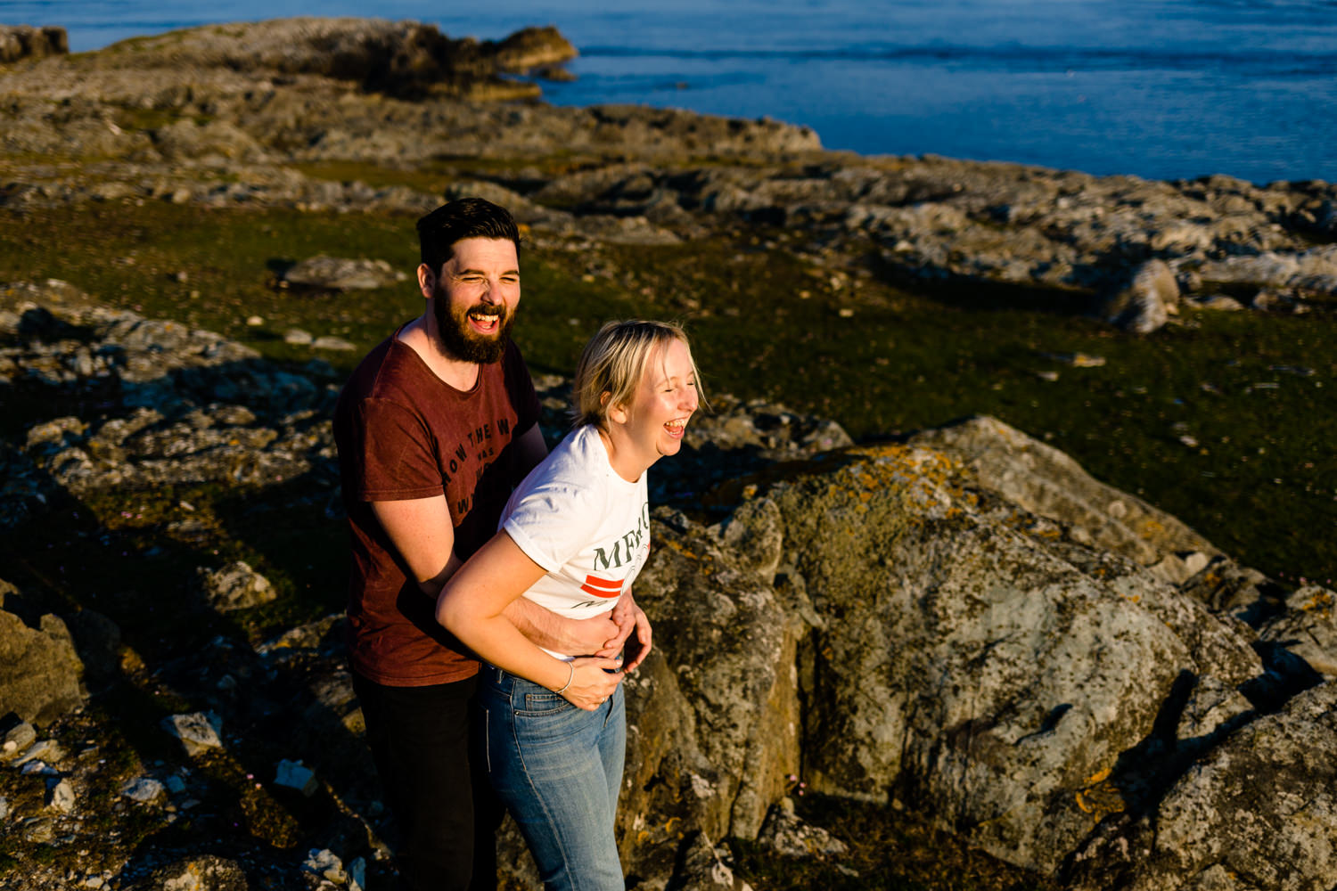 A couple laugh together lit by the golden hour sun on the headland in Anglesey.