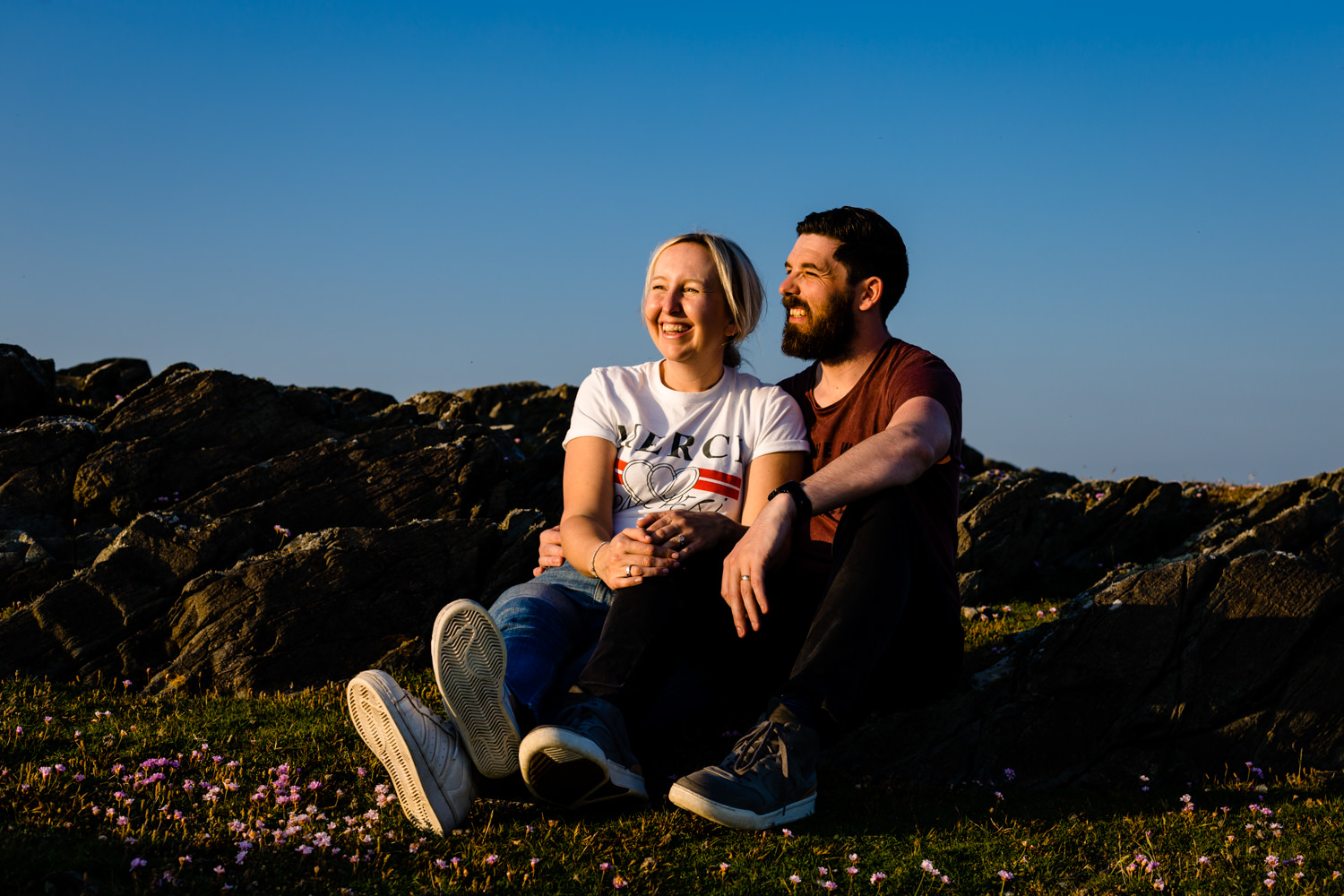 A couple sat watching the sunset on their pre wedding shoot, by Anglesey wedding photographers Zoe & Tom