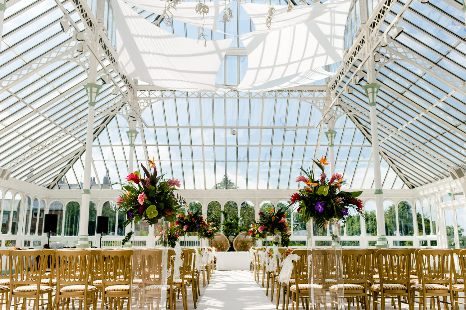 The Isla Gladstone in Liverpool set up for a wedding ceremony on a sunny day with tropical flowers.