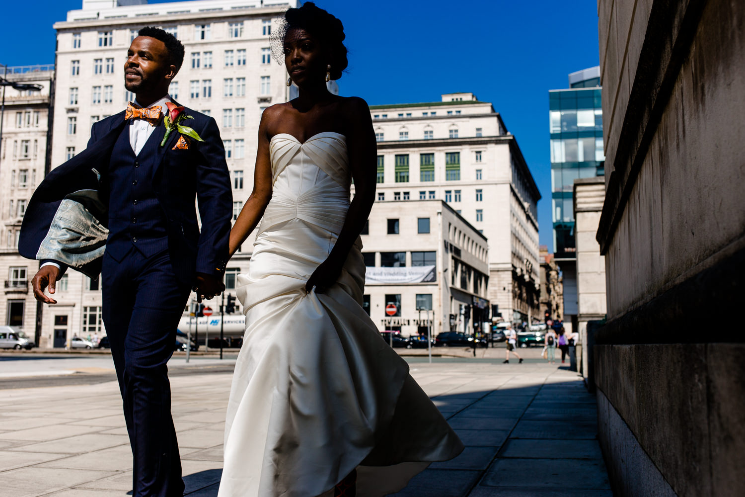 Bride and groom stroll the streets of Liverpool on their wedding day.
