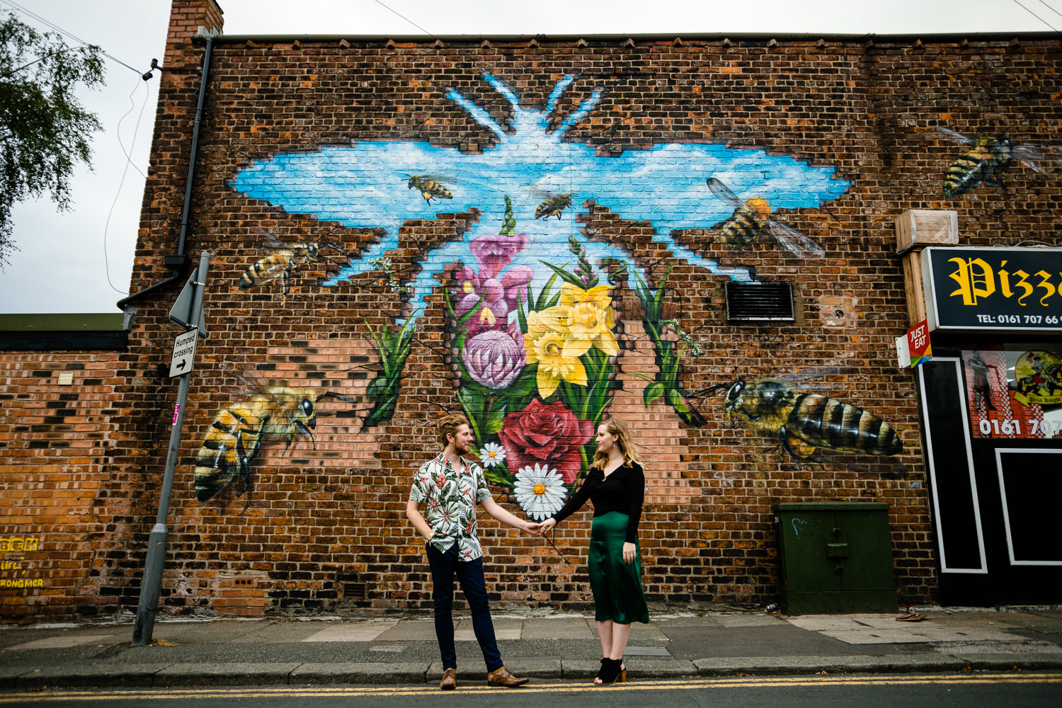 Rose & Josh stood in front of a colourful Manchester Bee wall mural in Monton, by colourful wedding photographers in Manchester.