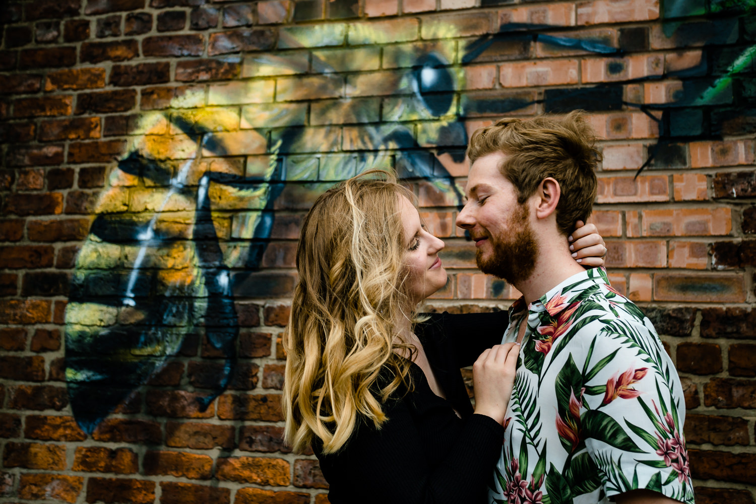 A couple cuddle in front of a graffiti bee in Monton, Manchester.
