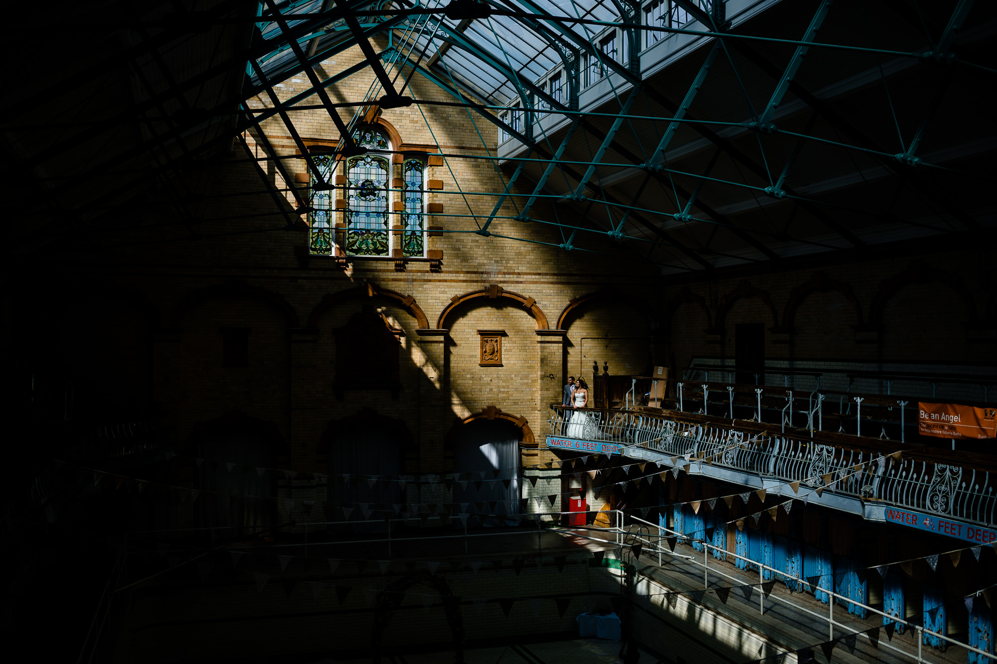 Kirtsy and Kirk bathed in light in the main Gala pool by Victoria Baths Wedding Photographers Zoe & Tom