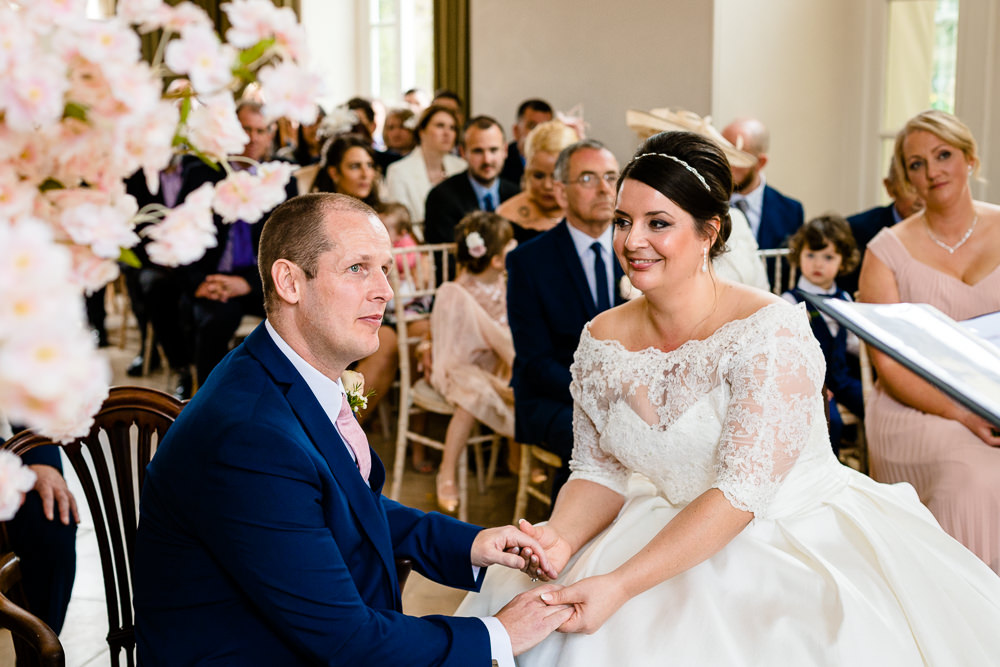 A bride and groom hold hands during their wedding ceremony at Iscyod Park.
