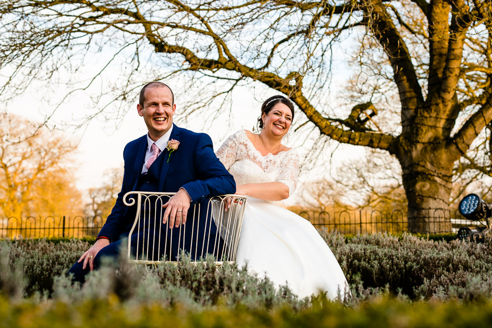 A laughing wedding couple sat in the Iscoyd Park garden, wedding photography by Zoe and Tom of About Today Photography