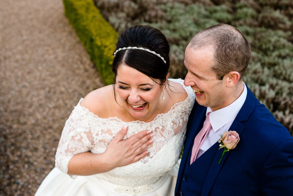 A bride laughing with her groom on their wedding day couple photography at Iscoyd Park.