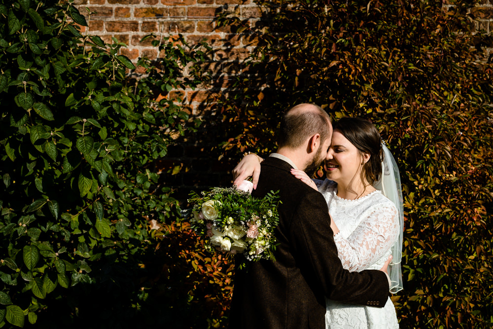 A Chester wedding at Trafford hall, colourful wedding photo of a bride and groom in front of autumnal leaves.
