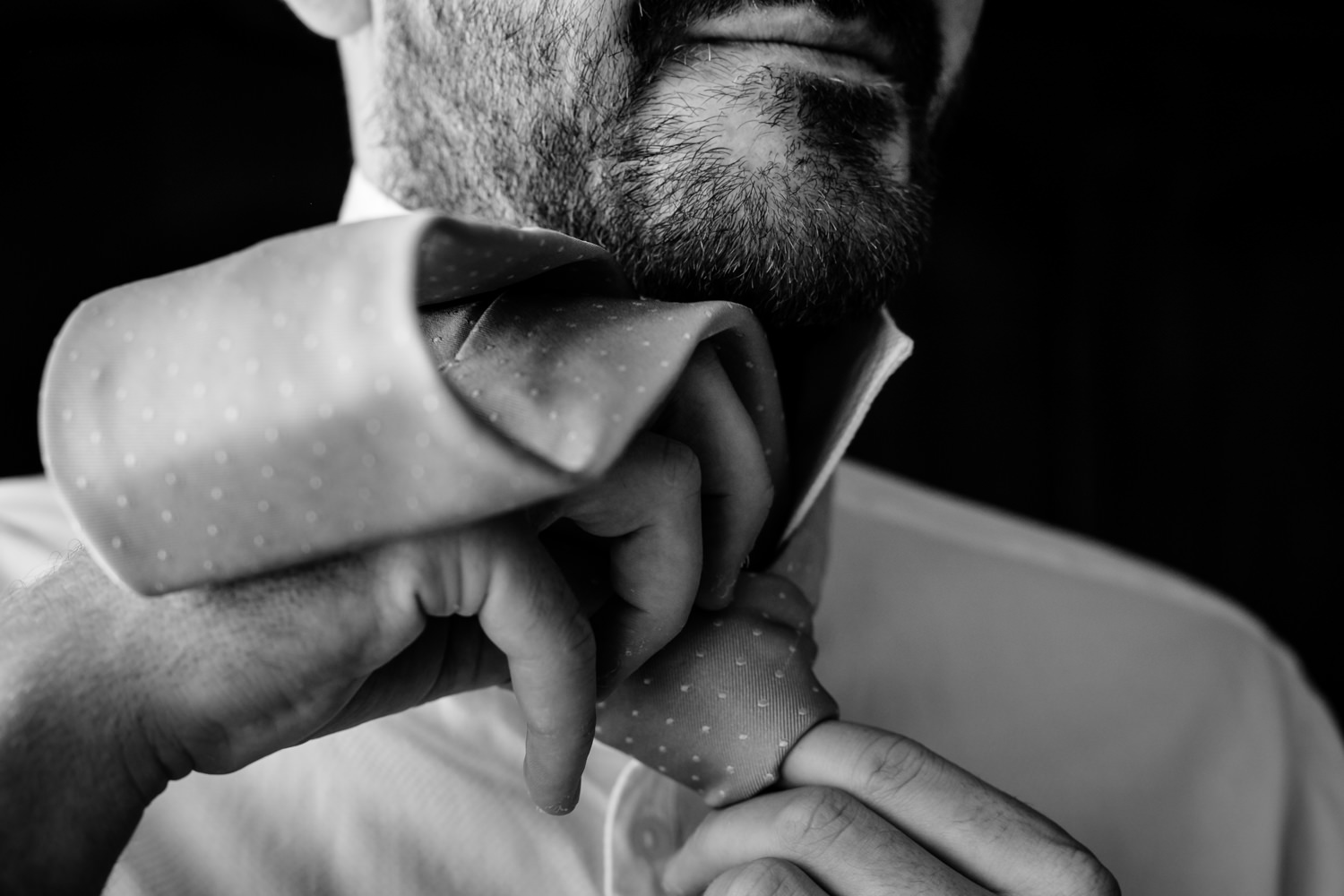 Groom knotting his tie.
