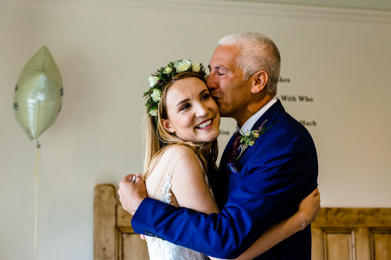 A father and daughter hug, wedding photographer Whirlowbrook Hall