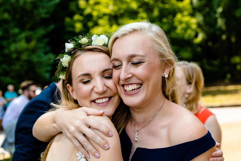 A bride and bridesmaid hug, wedding photograph Whirlowbrook Hall