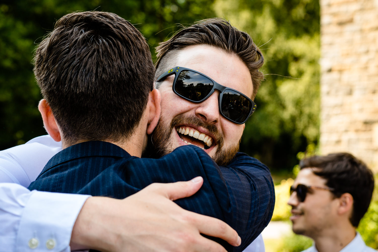 A guest smiling and hugging the groom.