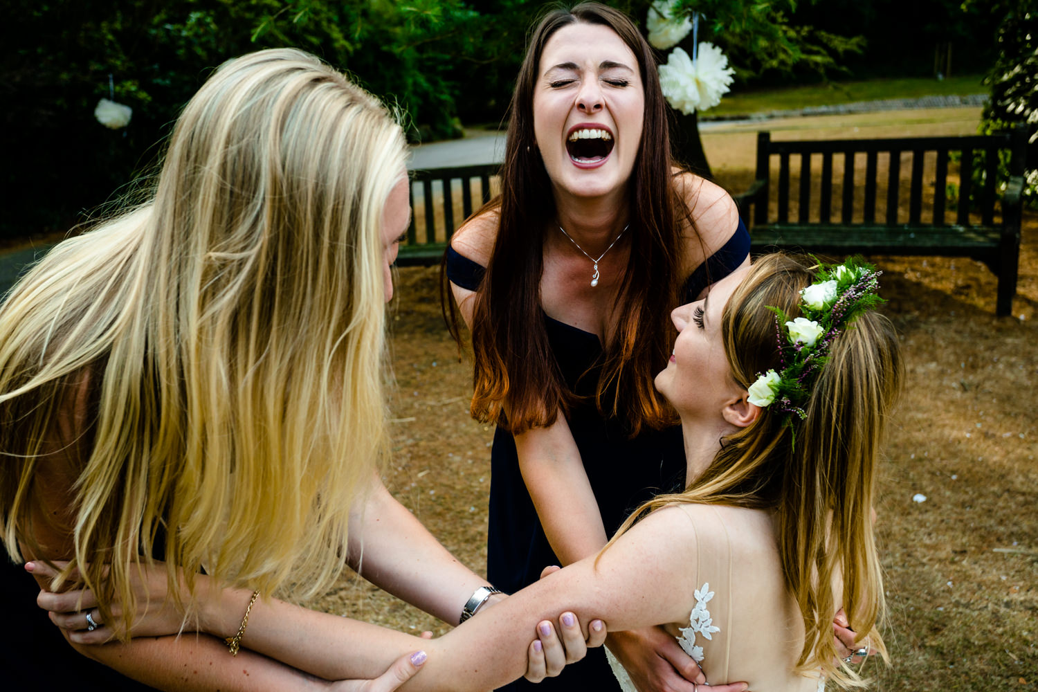 Bridesmaids laugh as they drop the the bride.