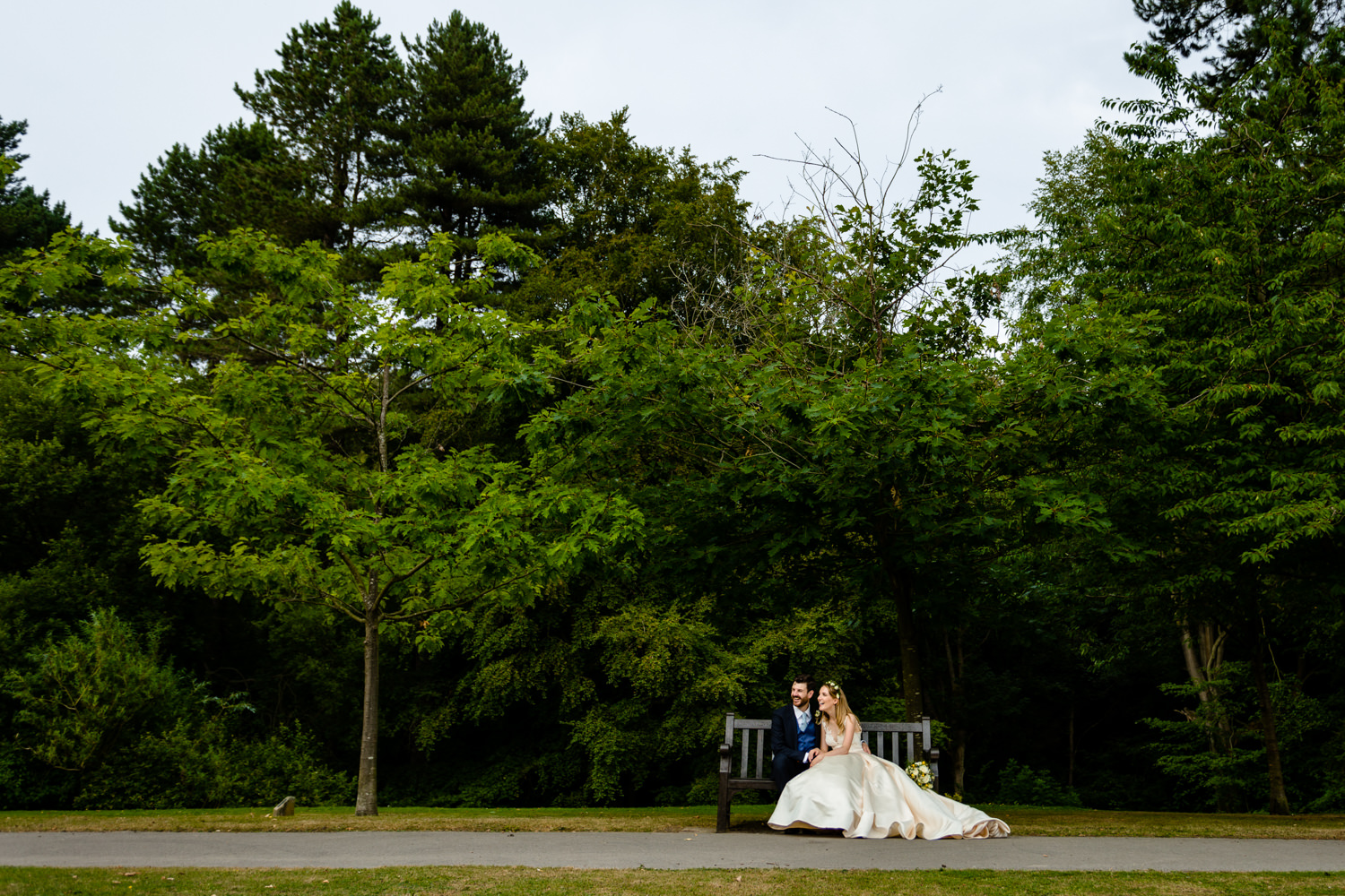 Bride and groom relaxing on a bench, wedding	photos	Whirlowbrook Hall
