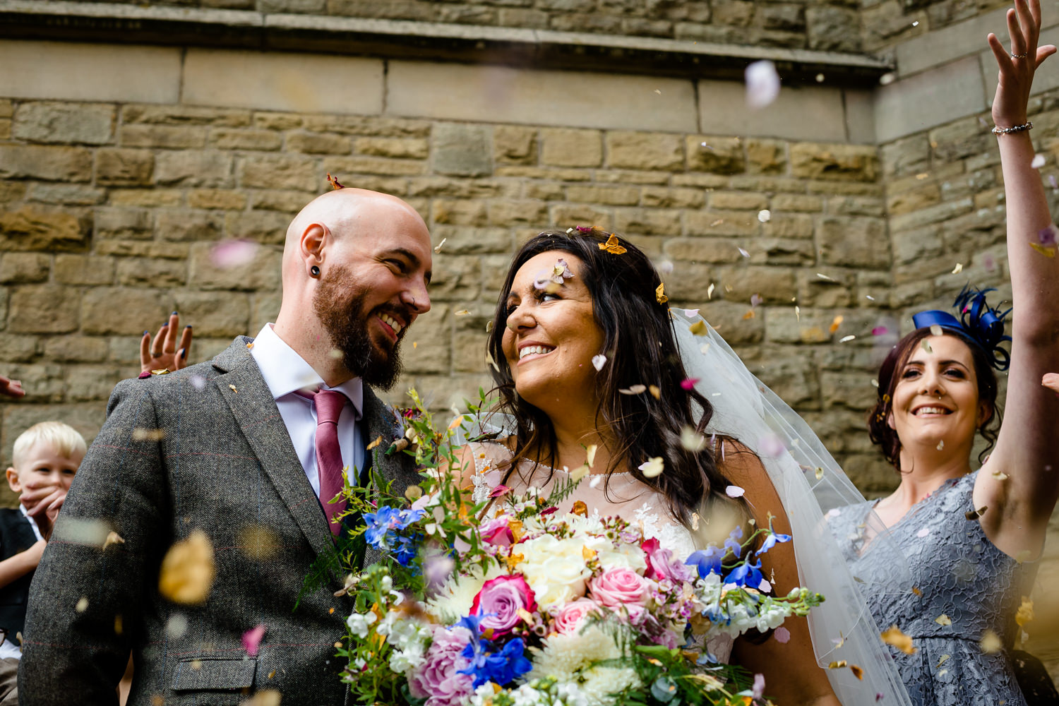A bride and groom smile at each other with confetti