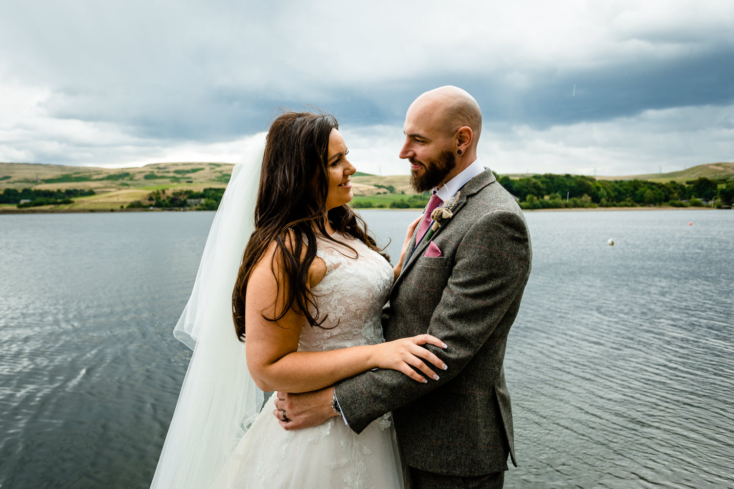 wedding photographer Rochdale, a bride and groom by Hollingworth Lake in the rain