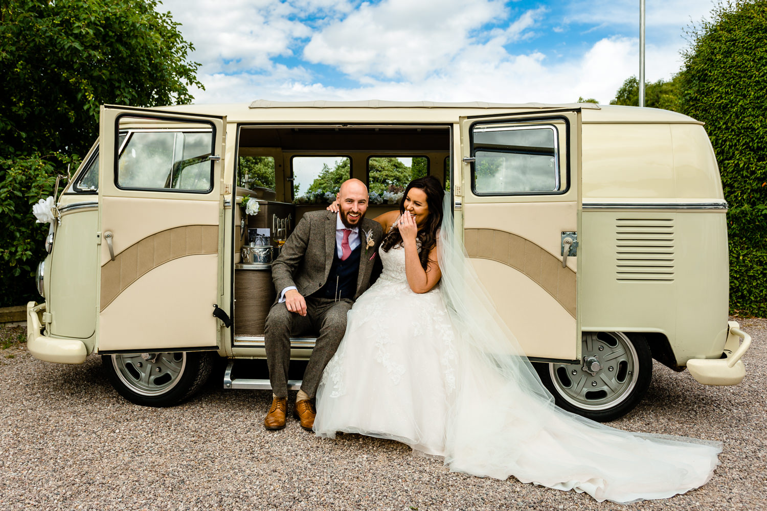 wedding photography Rochdale, a bride and groom lughing together in their vintage VW campervan