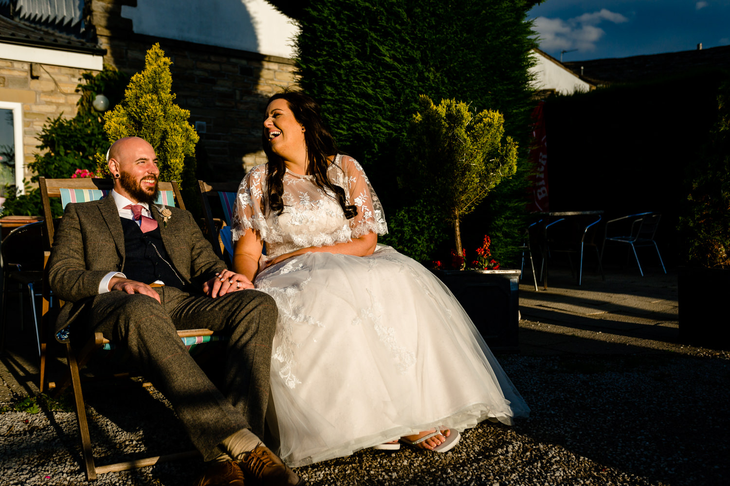 A bride and groom sat on deckchairs at sunset, relaxed Rochdale wedding photos