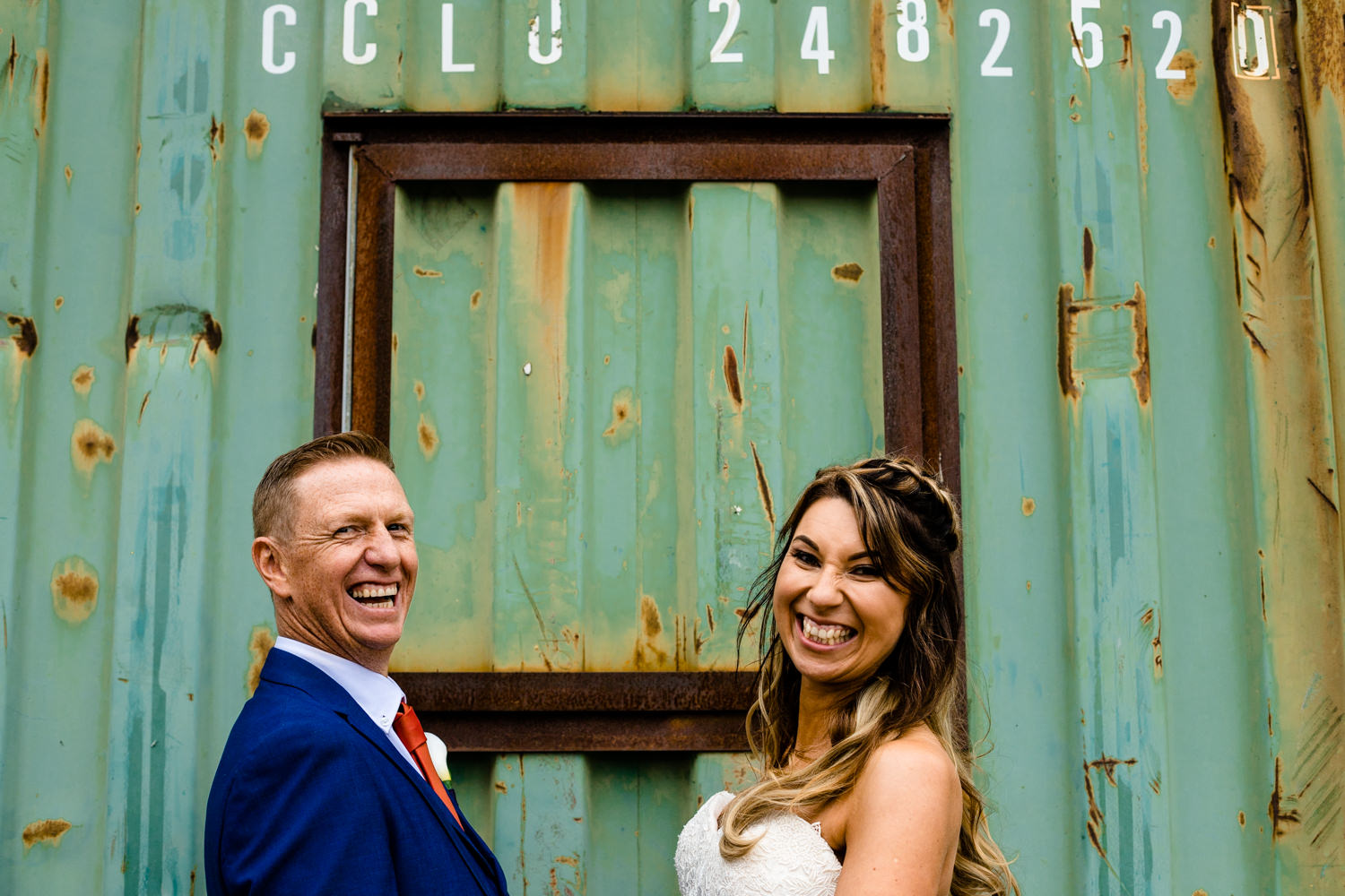 A bride and groom laughing in front of an industrial  container, relaxed wedding photograph Victoria Warehouse