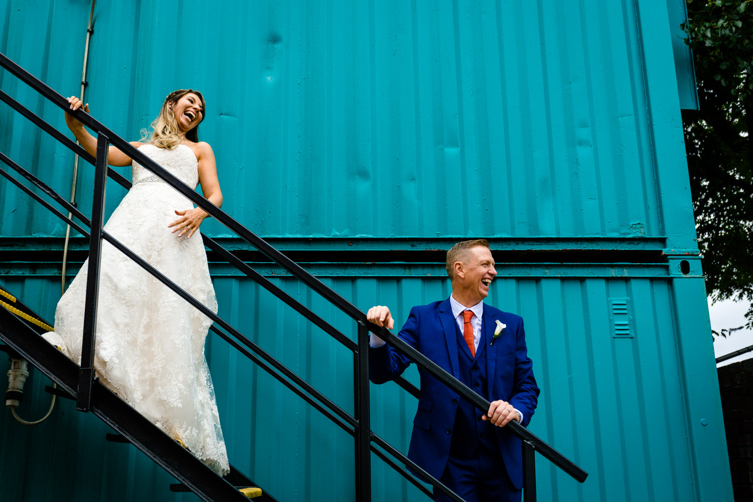 A bride and groom laughing in front of a bright blue container at Victoria Warehouse, colourful wedding photographers