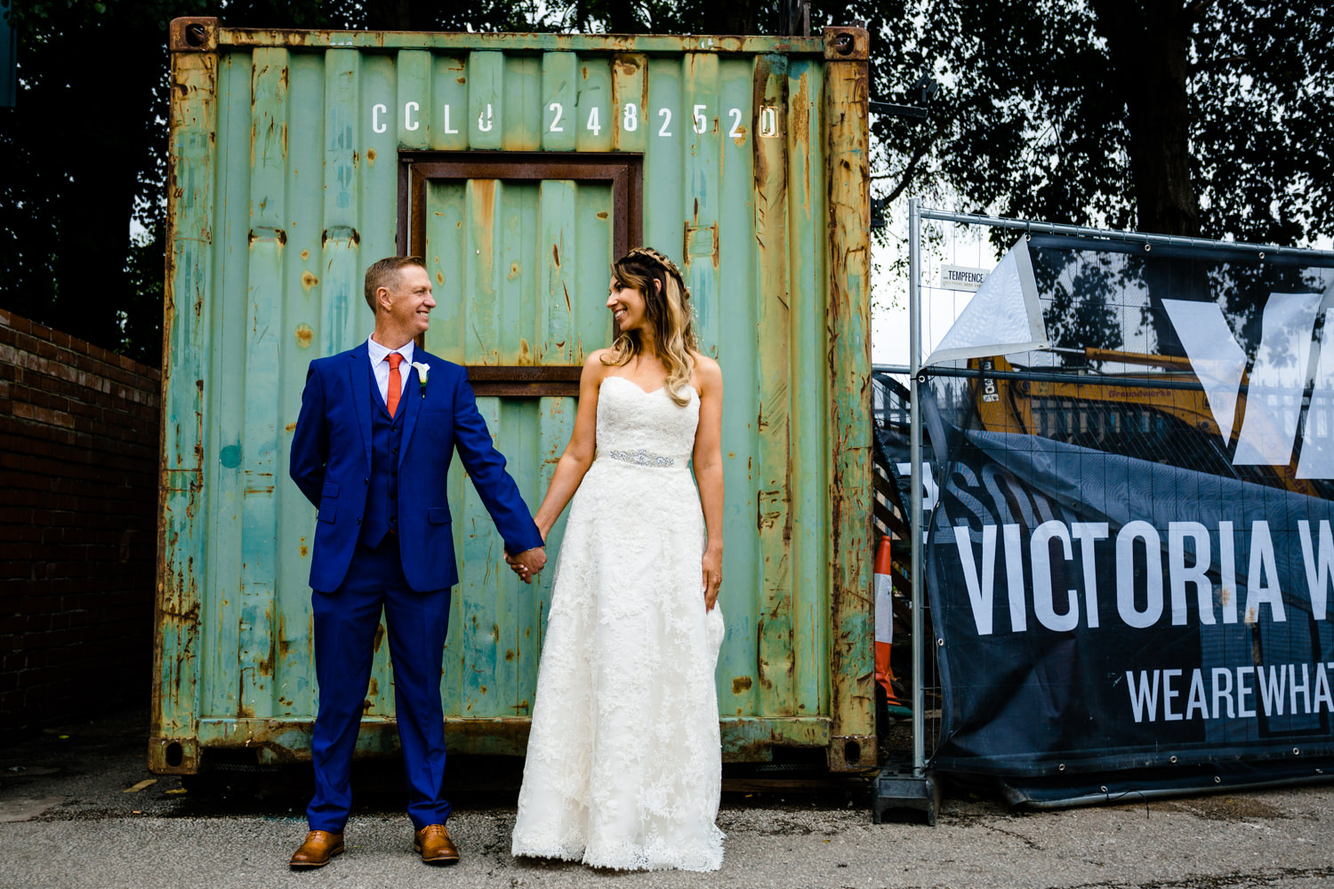A bride and groom holding hands at Victoria Warehouse wedding photograph