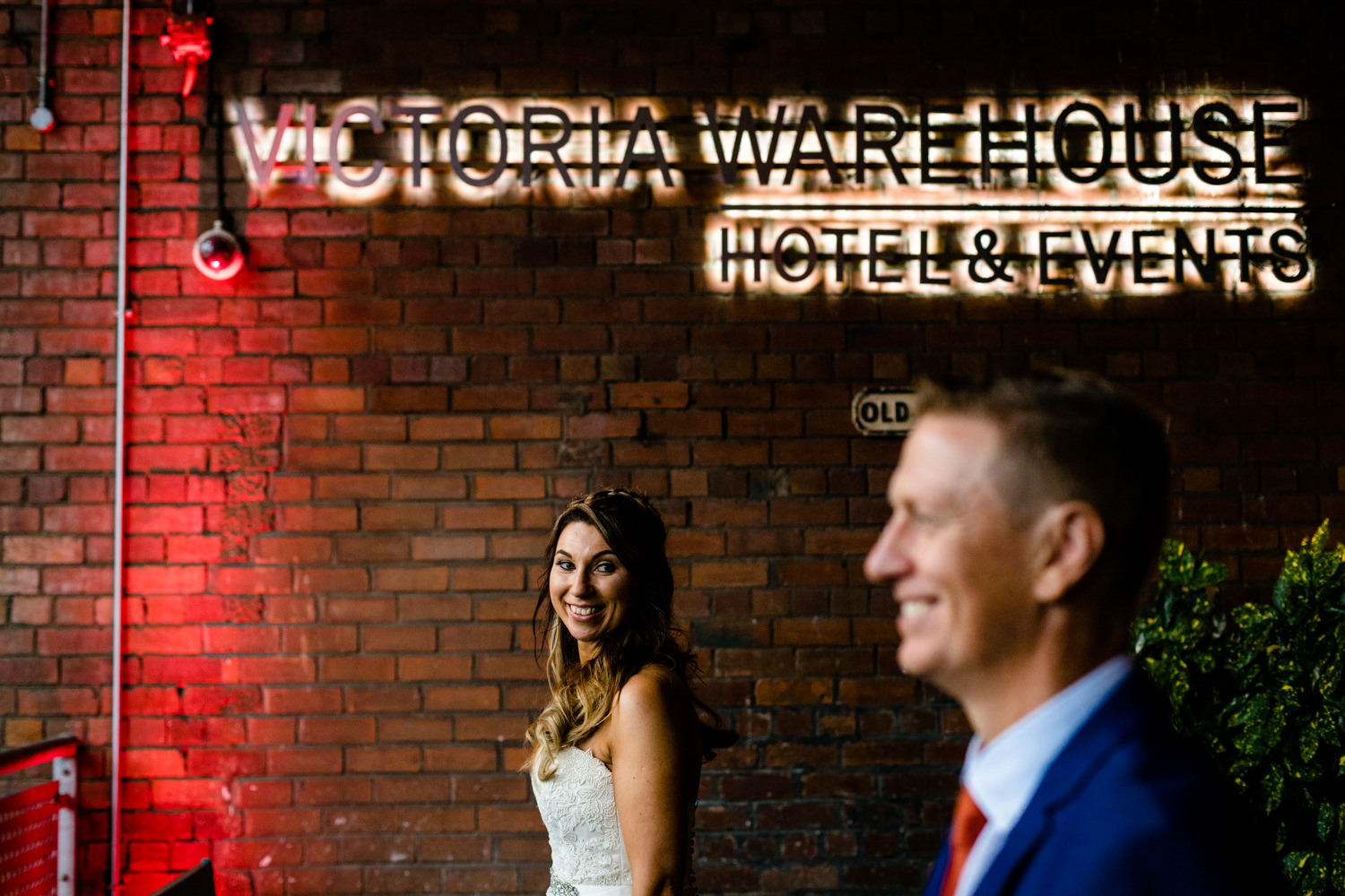 wedding photographer Victoria Warehouse, a bride looks at her groom under the neon sign