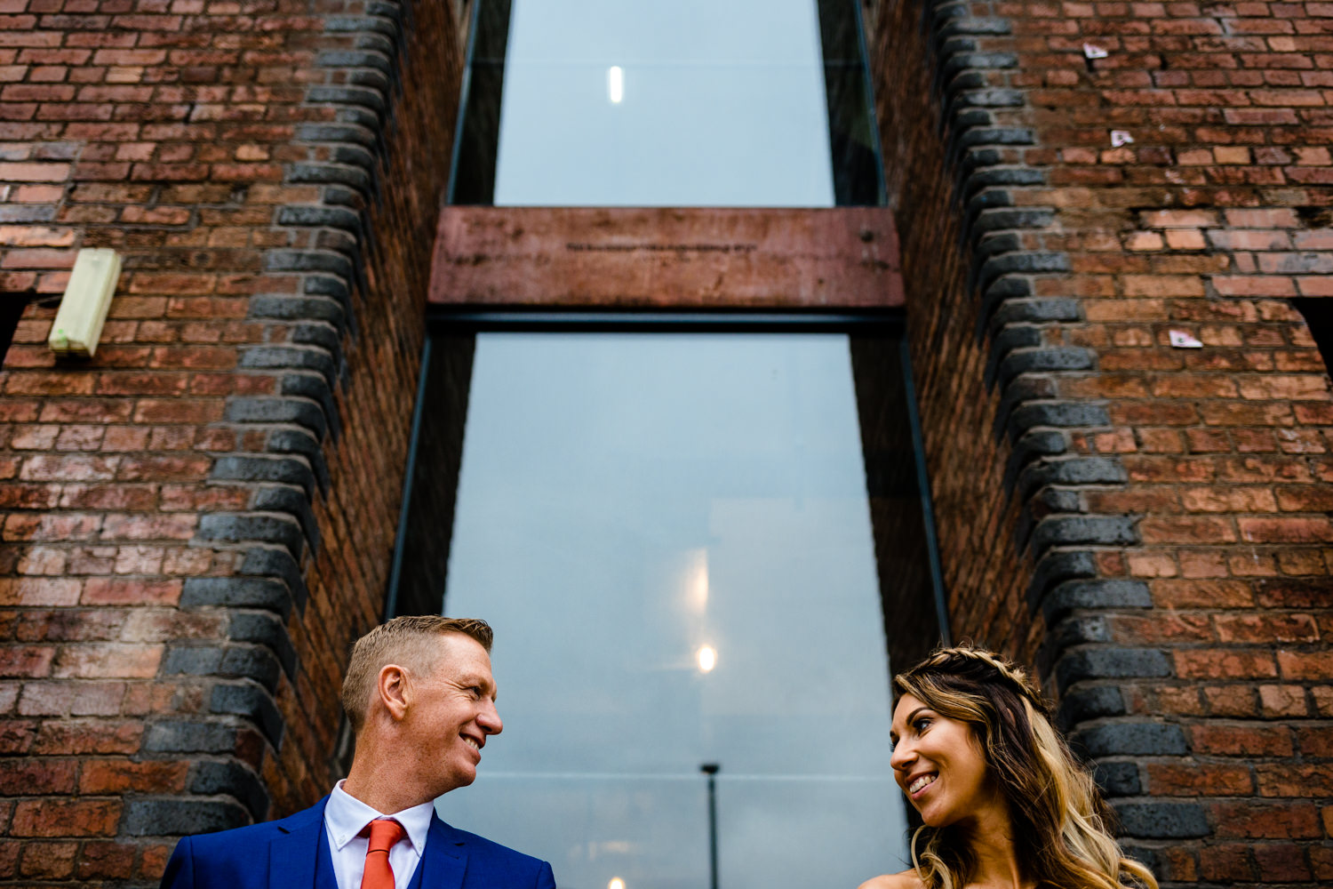 A bridge and groom in front of the brick facade of Victoria Warehouse wedding photographs