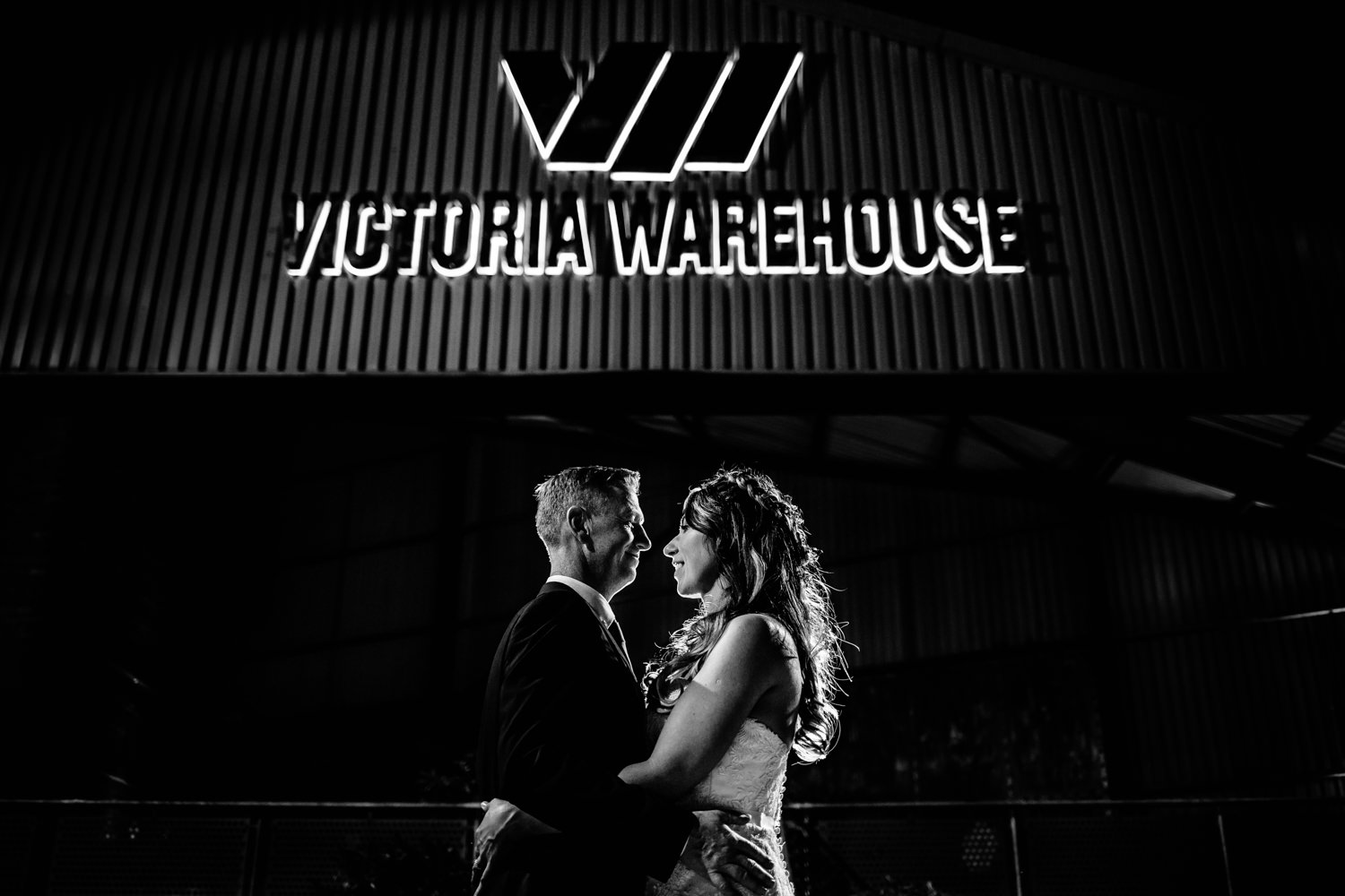 Black and white image of a couple in front of the illuminated sign at Victoria Warehouse by wedding photographers Zoe and Tom.