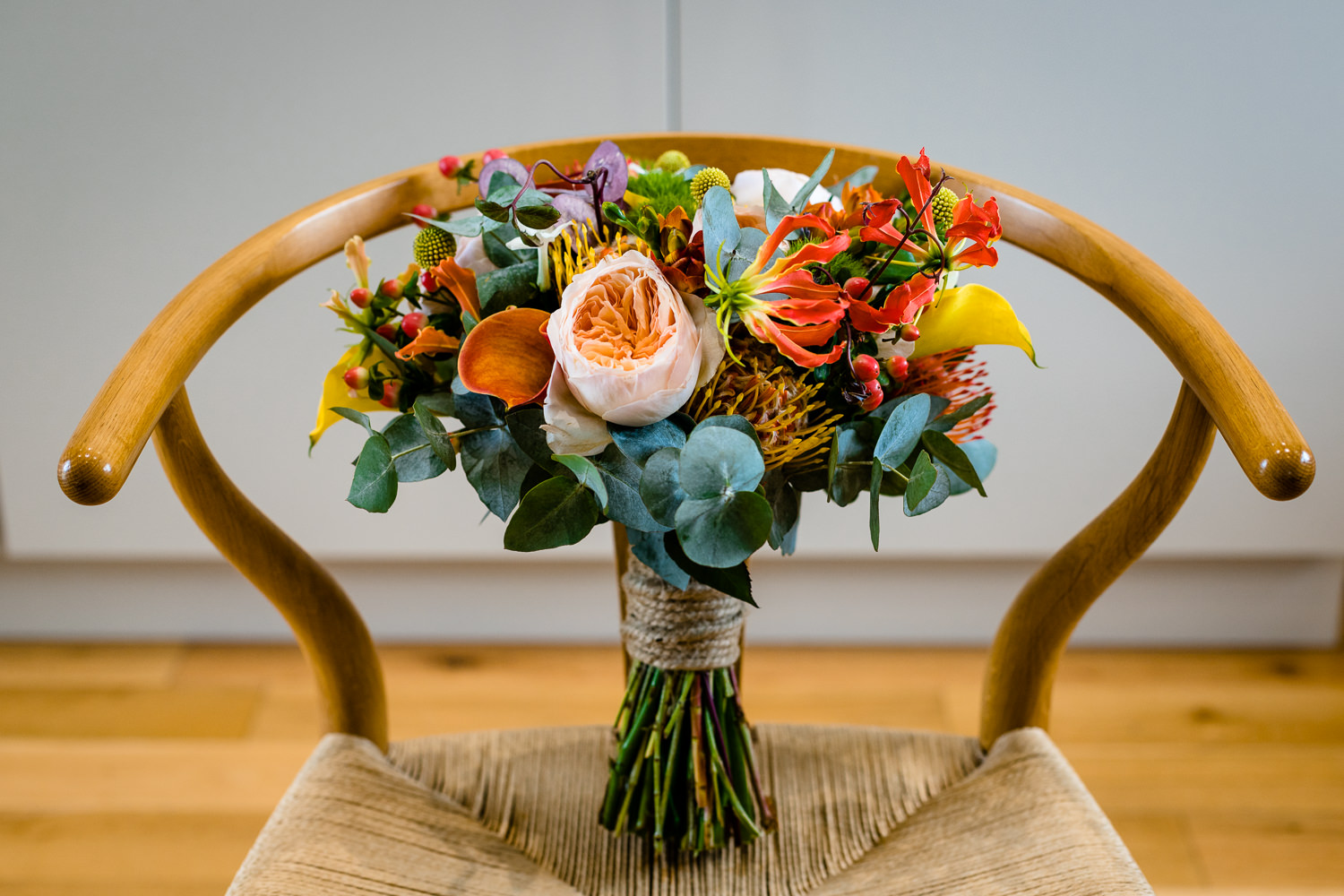 Colourful bouquet on a wishbone chair, Anglesey wedding photography