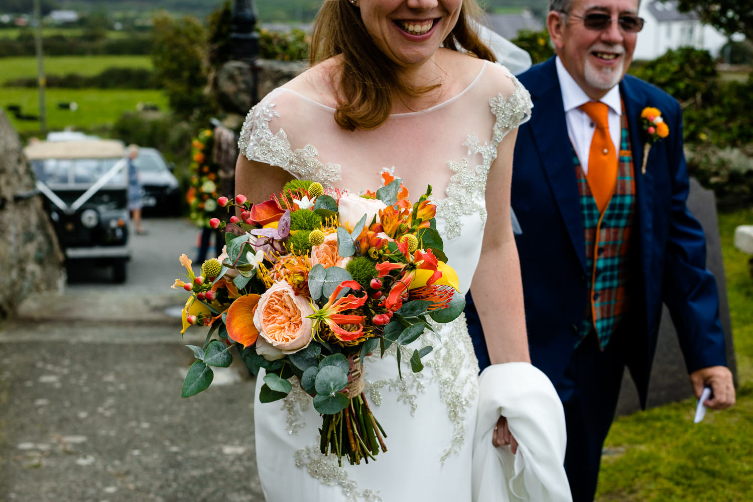 A bride carrying a bright bouquet on the way to church, Colourful Anglesey wedding photos