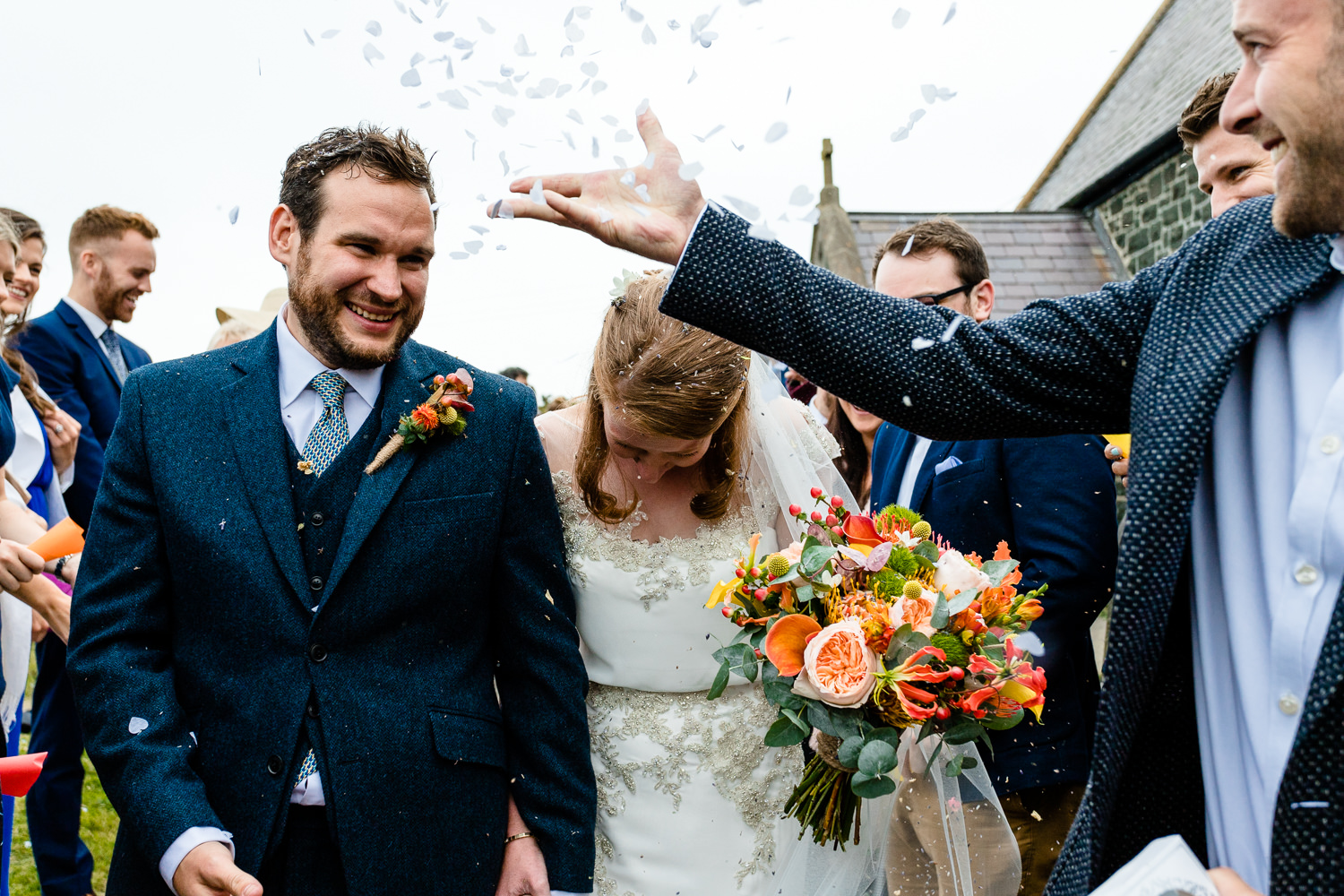 Confetti being thrown at a bride and groom, Colourful	Anglesey wedding photography