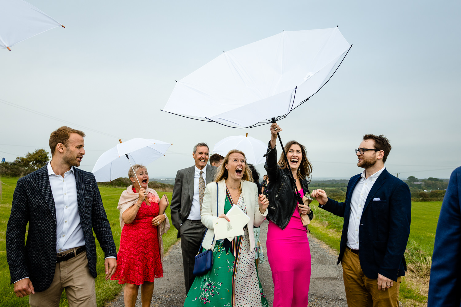 A wedding guest laughs as her umbrella turns inside out in the wind relaxed Anglesey wedding photography