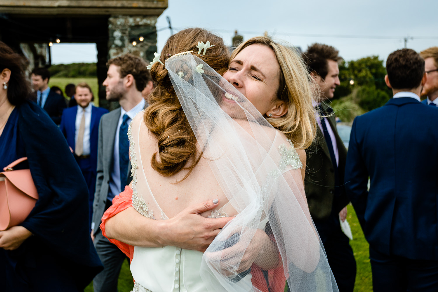 A guest hugs the bride, relaxed Anglesey wedding photographer