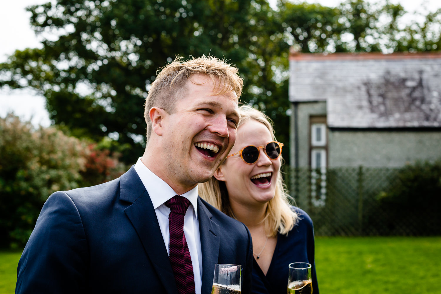 relaxed	Anglesey wedding photograph of guests laughing