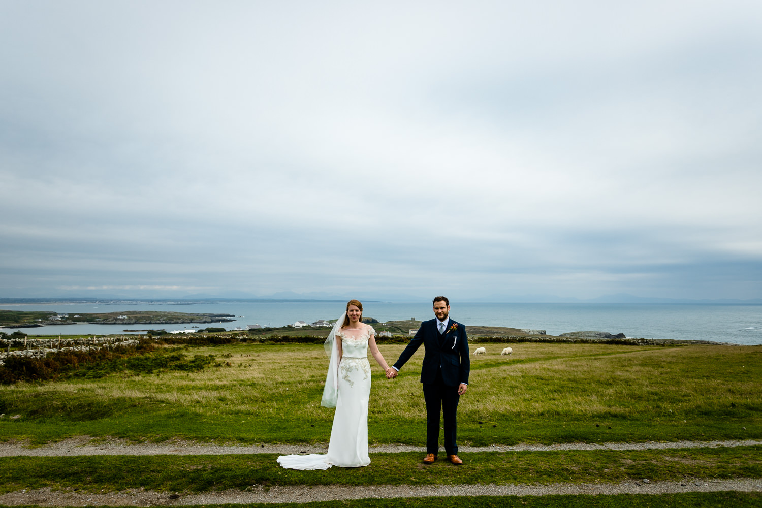 A bride and groom stood on the Rhoscolyn headland by an Anglesey wedding photographer