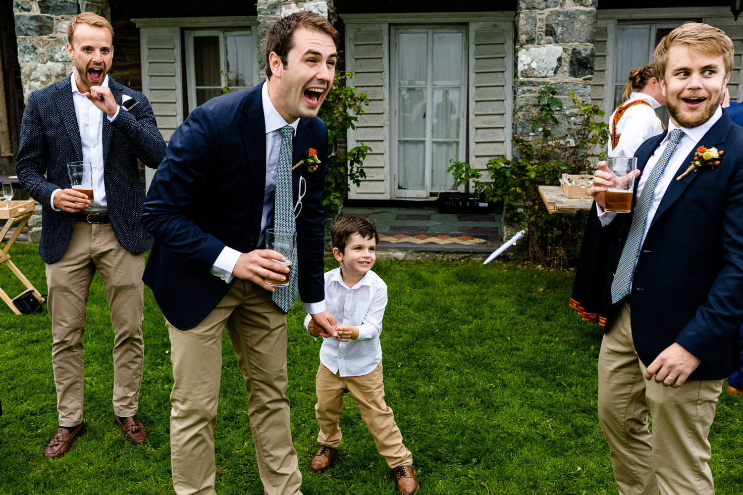 A groomsman laughing at what a young boy  has said, relaxed Anglesey wedding photo
