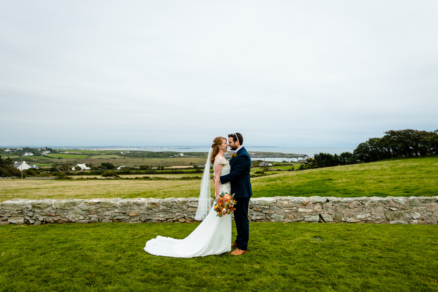 A bride and groom facing each other in front of the bay at Rhoscolyn, Colourful Anglesey wedding photographers