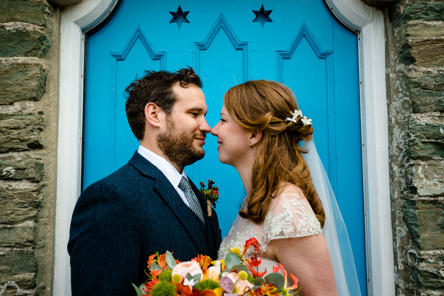 Anglesey wedding photographs of a bride and groom in front of a bright blue doorway in Rhoscolyn