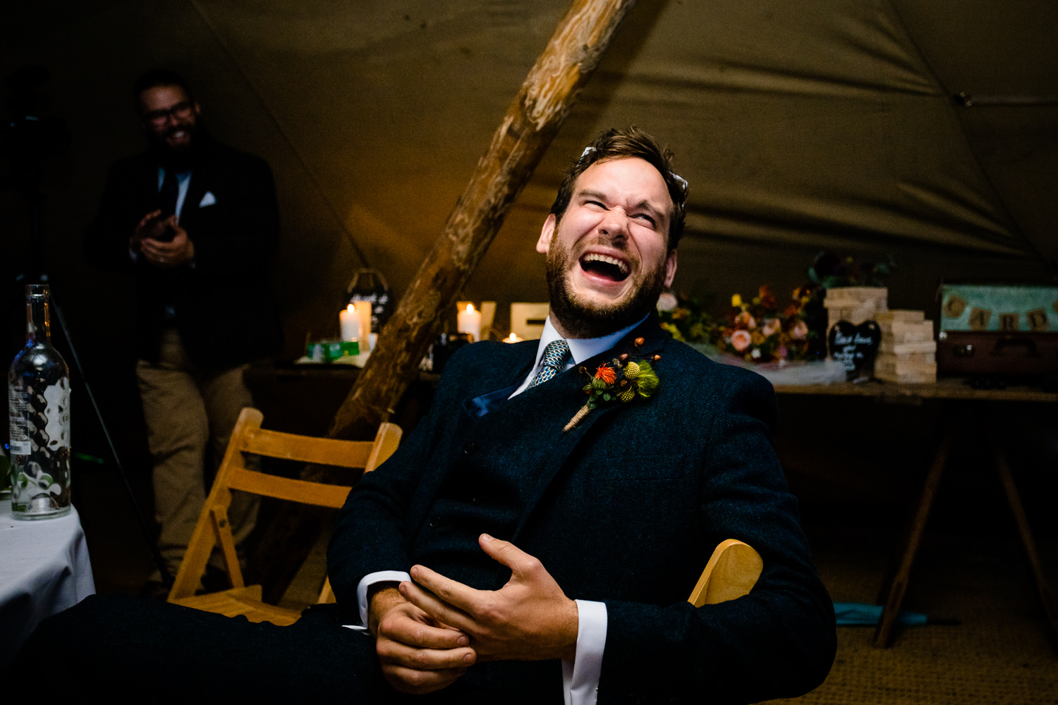 A groom laughs at his best mans speech, relaxed Anglesey wedding photos