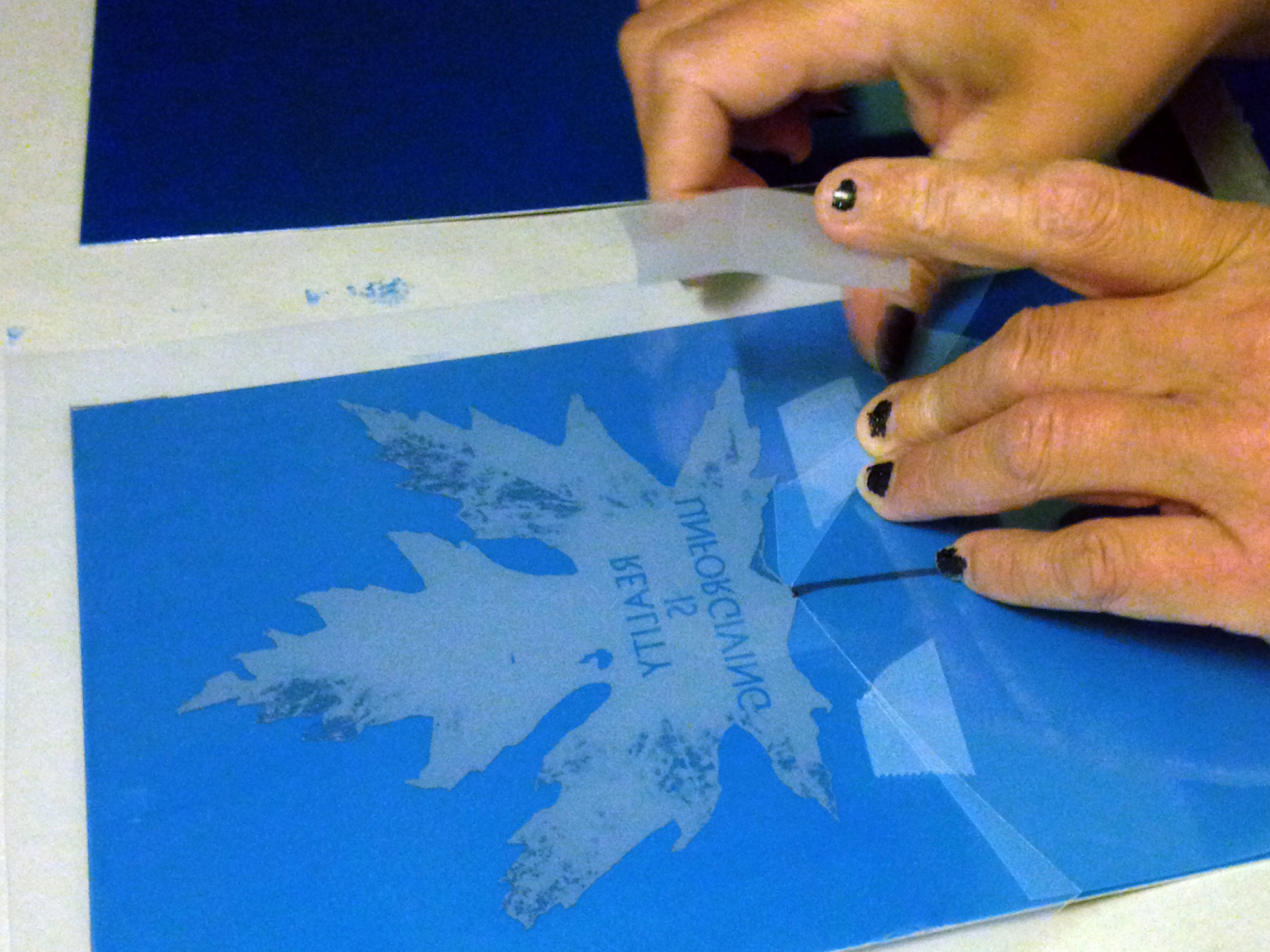 Etching plate is coated in light sensitive emulsion. The film is placed, and exposed to UV light as a negative image