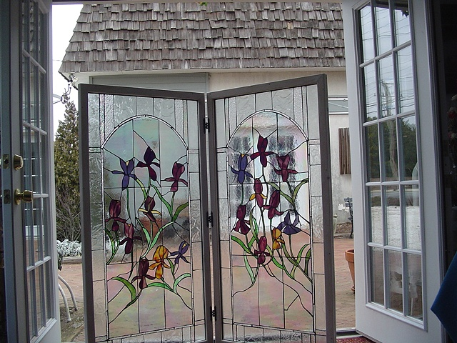 """""""Irises""""  Stained Glass  This panel was originally designed to be a screen for a large wine cooler. Once it was completed, however, my clients decided it was too pretty to place where they wanted to put it. The panels are whitewashed and framed in oak. They are joined together with hinges and can stand freely. The owners commissioned SwellColors to make them another panel for the original space.  Designing and fabrication typically are all done in our studio located on Long Beach Island, NJ. Custom work is one of our specialties, evidenced by our many happy repeat clients. We have a team of carpenters working with us for all your installation needs as well."""