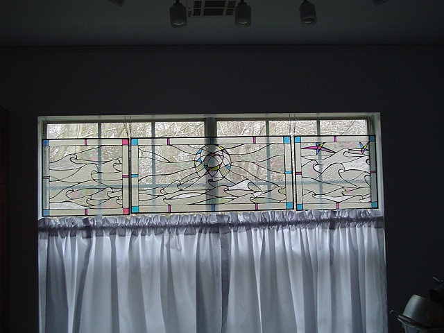 Morning, Noon, Night  Stained Glass  This piece is one of three panels. The colors you see amidst the clear textured glass is irridized and dicroic glass. All the panels pictured change a great deal throughout the day depending upon the interior and exterior lighting conditions.  It is held in private collection in Tinton Falls, NJ.  Designing and fabrication typically are all done in our studio located on Long Beach Island, NJ. Custom work is one of our specialties, evidenced by our many happy repeat clients. We have a team of carpenters working with us for all your installation needs as well.