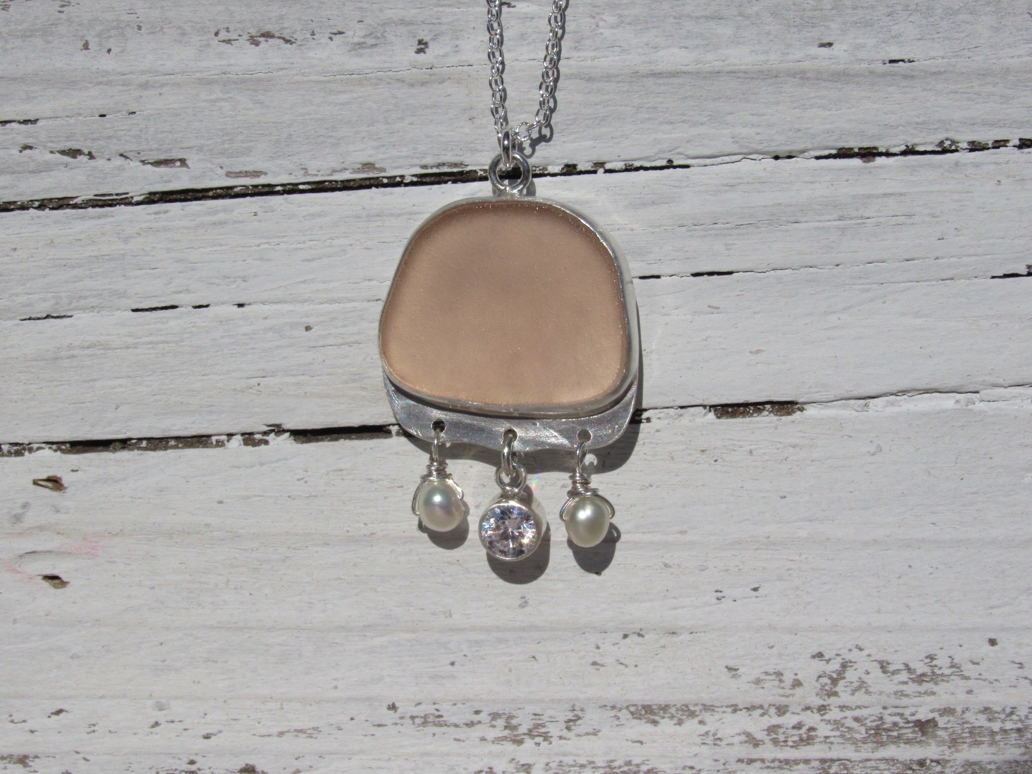 A lovely custom gift made by artisan, Ceire Parker, here at SwellColors. A gorgeous pink piece of sea glass pairs lovely with saltwater pearls and a sparkly cz. Handmade in solid silver.