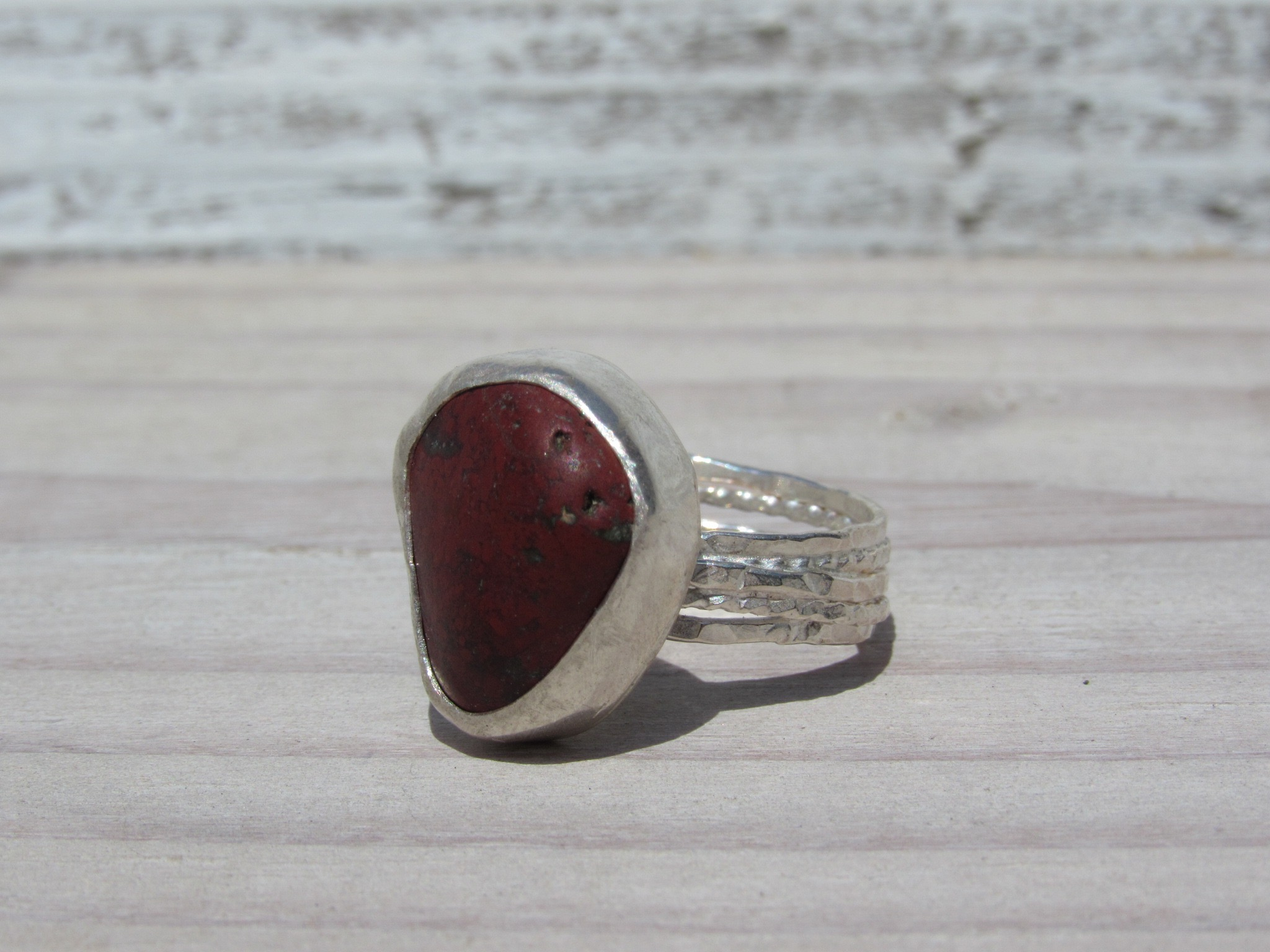 Crimson red beach stone ring set in sterling silver with a twisted multiband.