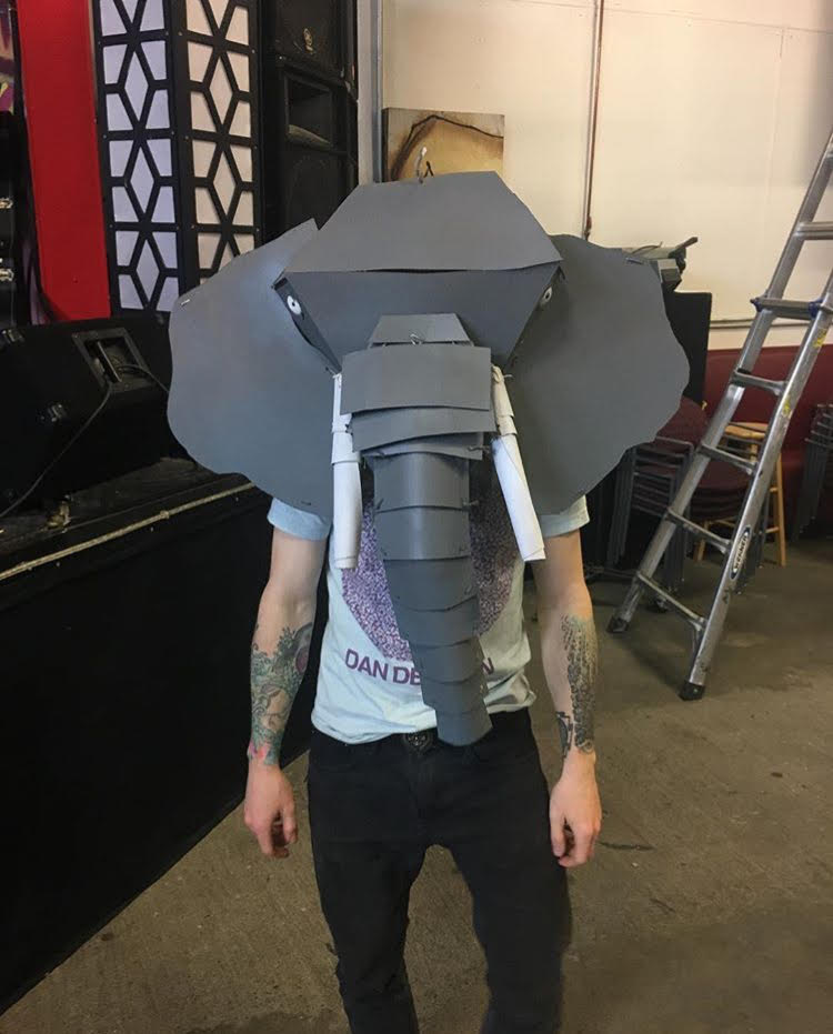 Wearable elephant mask constructed out of chipboard, glue and string, colored with spraypaint.